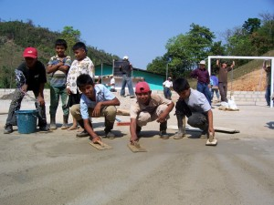 Guatemalan volunteers paving the pitch with smiles on their faces.